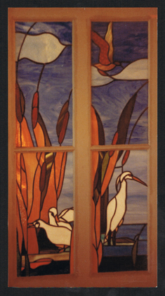 Four leaded stained glass panels for an interior door between the bathroom and a hallway. The scene lights up when there is someone in the bathroom. The scene is a marshy area with a snowy egret, white ducks and cattails against a background of blue sky and sea.
